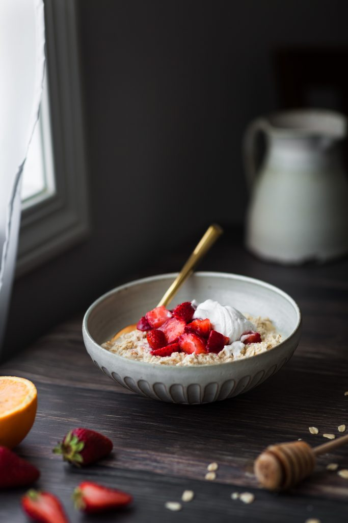 head on image of a bowl of vegan strawberries and cream bircher museli sitting by a window.