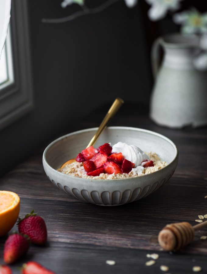 A head on image of a bowl of bircher museli with strawberries sitting by a window with flowers in the foreground.