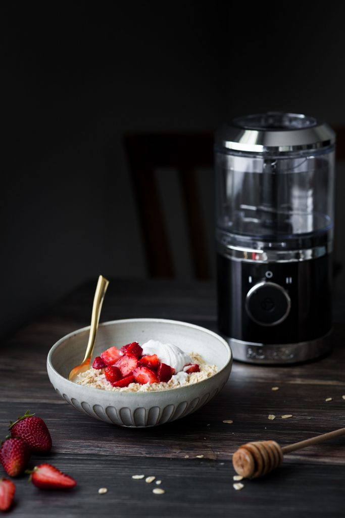 head on image of strawberry vegan bircher museli with a golden spoon and a small food processor in the background..