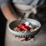 a head on image of a baker holding a bowl of bircher museli in a cermaic bowl with a gold spoon.