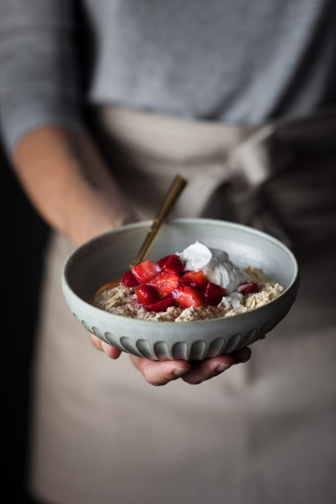 head on image of a person holding a bowl of strawberry and cream bircher museli.