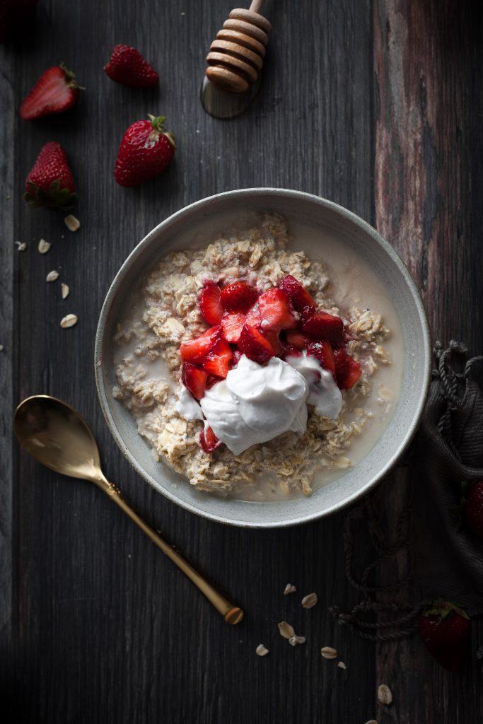 overhead image of a bowl of strawberry vegan bircher museli on a wooden backdrop.