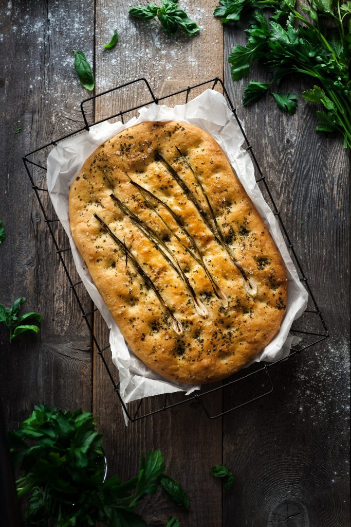 overhead image of baked focaccia in a wire bread basket.