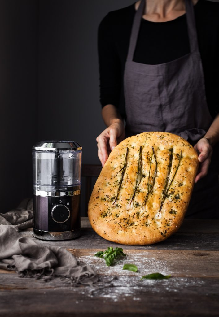 head on image of baker holding a focaccia bread with a small food processor to the left.