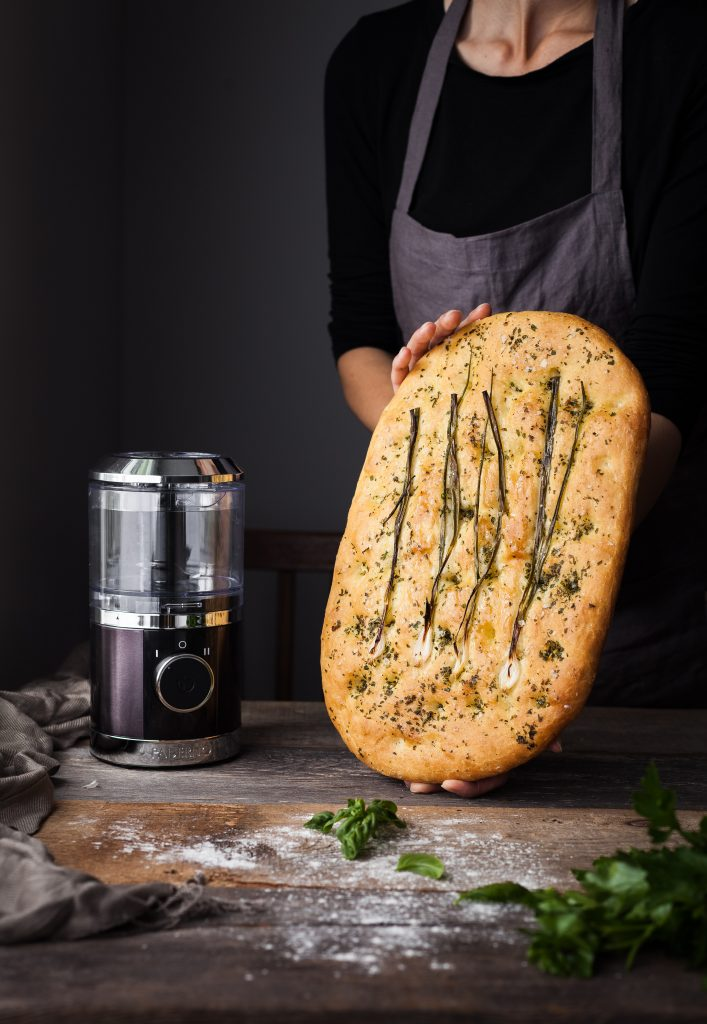 head on image of baker holding a focaccia bread with a small food processor on the left.