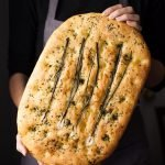 a head on image of a baker holding a loaf of focaccia bread.