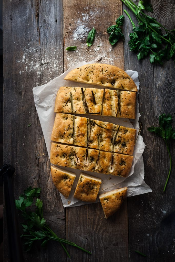 overhead image of focaccia bread sliced into squares.