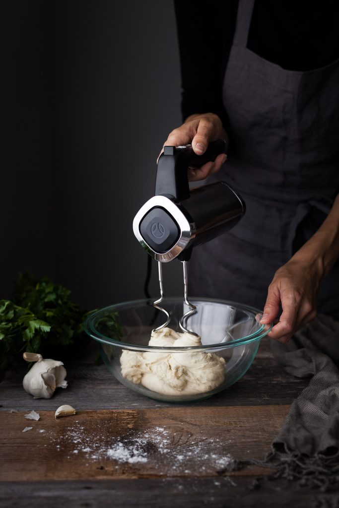 head on image of a baker kneading dough with a handheld mixer.