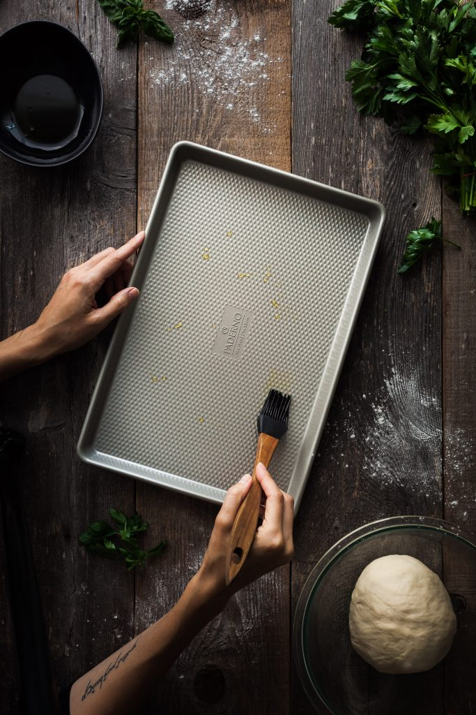 an overhead image of a baker brushing a pan with olive oil