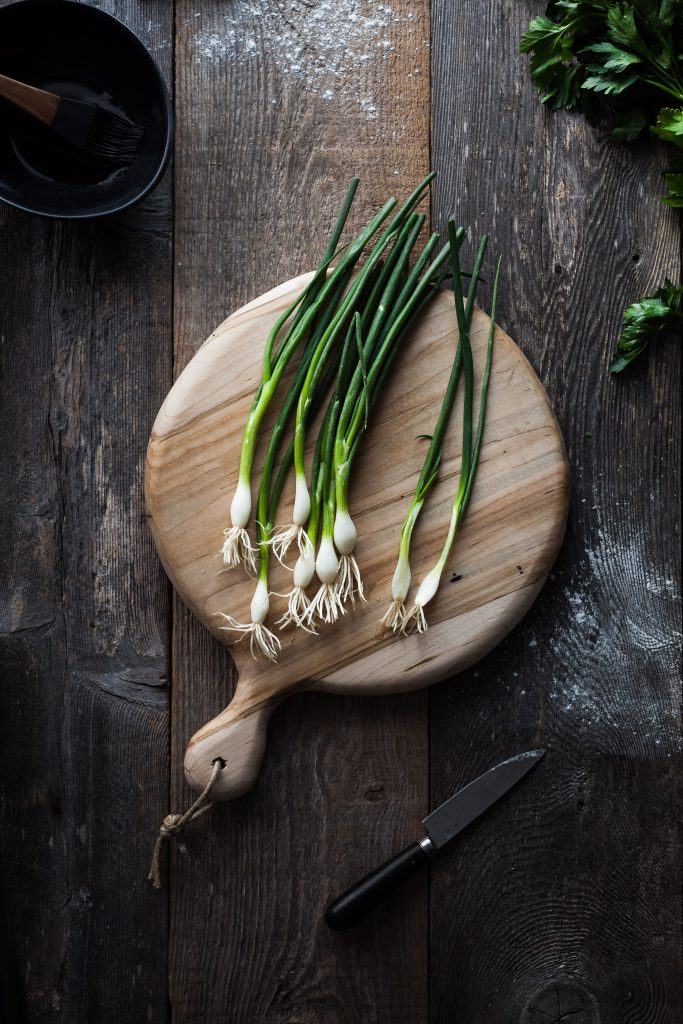 overhead view of green onions and a cutting board with a knife.