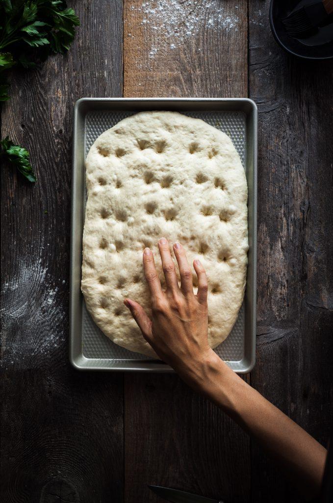 an overhead image of a baker dimpling focaccia bread dough.