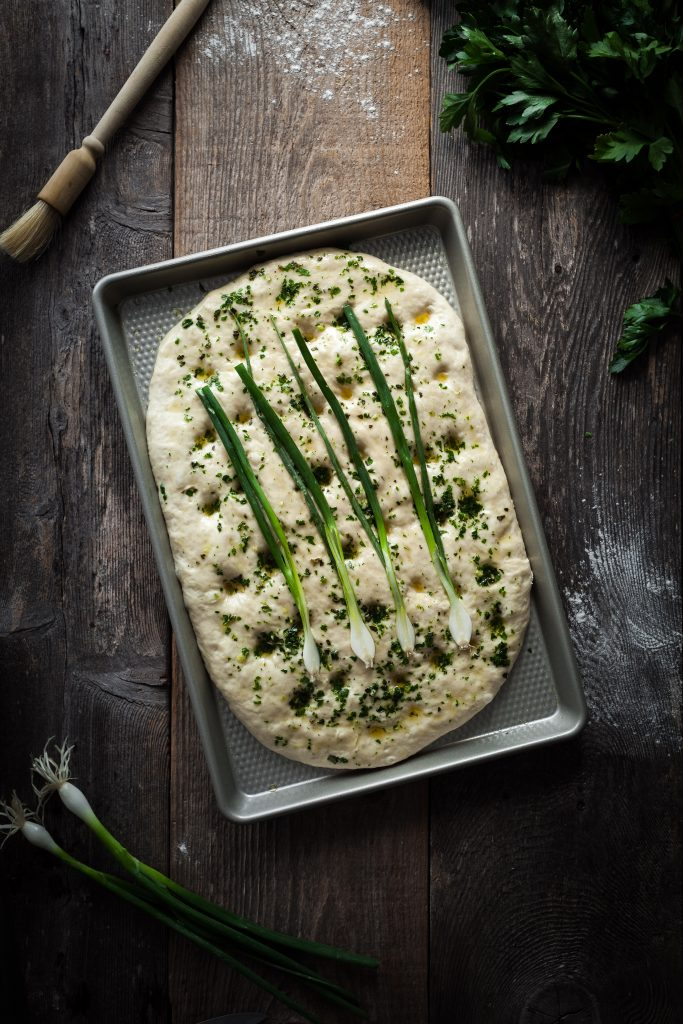 overhead image of focaccia on a baking sheet.