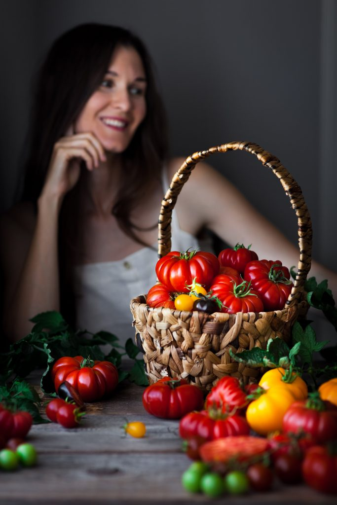 a portrait of Heidi Richter in a white camisole sitting behind a basket of tomatoes.