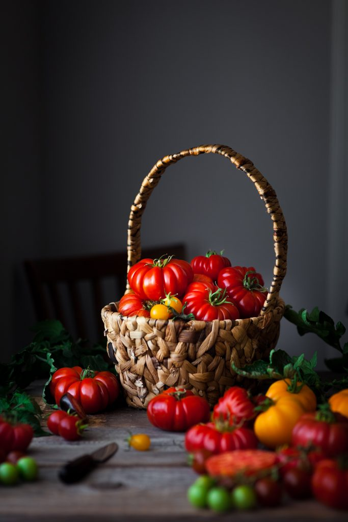 portrait of a basket of heriloom tomatoes spilling over onto a wooden surface.