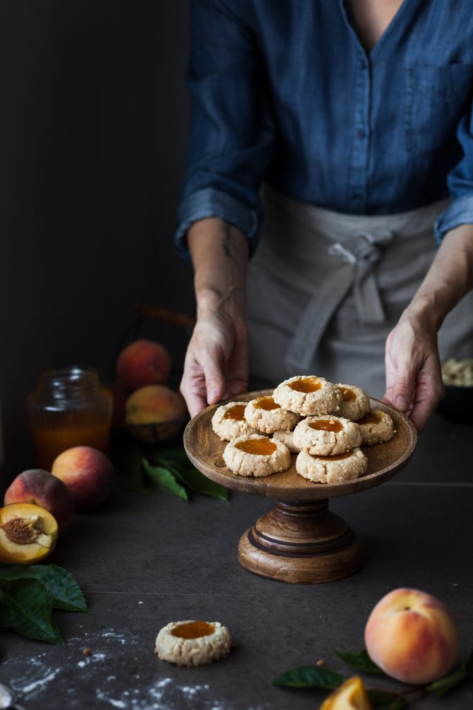 a head on image of a baker holding a small tray of vegan thumbprint cookies.