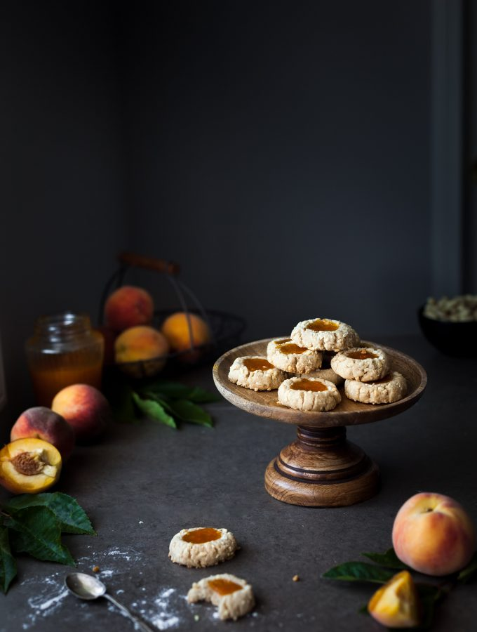 a head on image of a cookie stand with thumbprint cookies ontop with peaches and jam in the background.