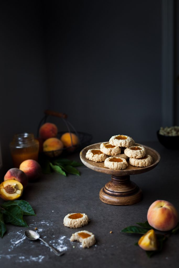 head on image of vegan thumbprint cookies sitting on a wooden cake plate with peaches in the background.