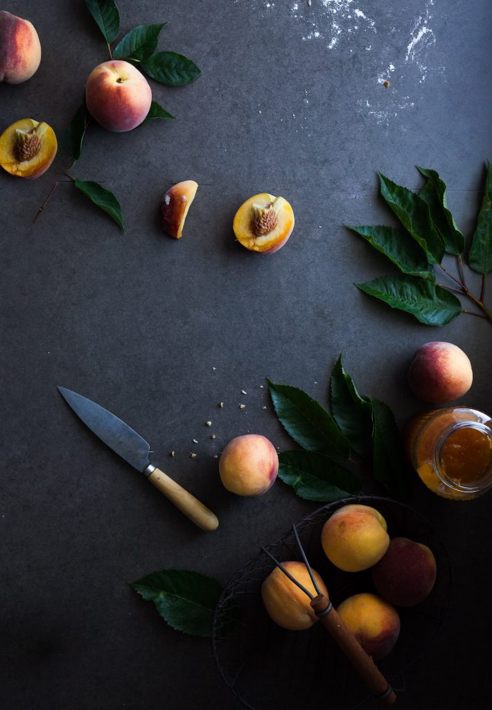 overhead image of sliced peach on a blue backdrop and a paring knife off to the side.