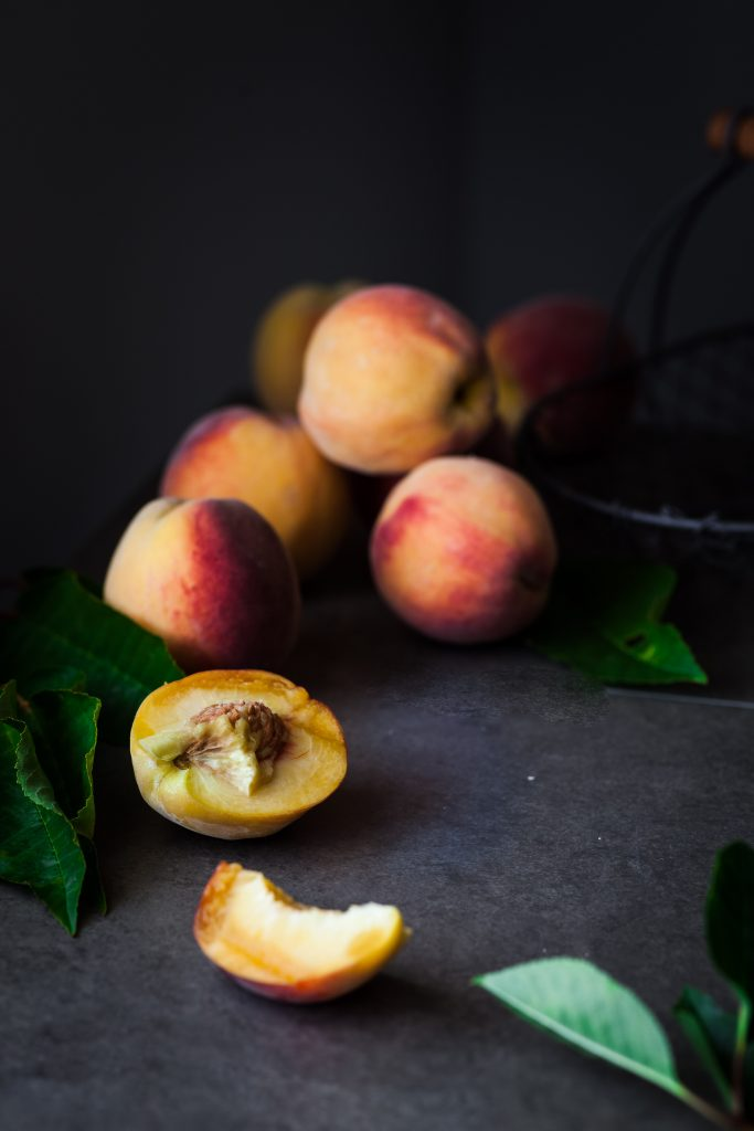 a close up image of a basket of peaches.