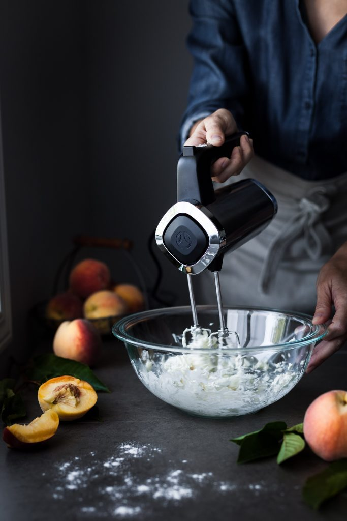 a head on image of a baker using a hand mixer to processor cookie dough in a bowl.