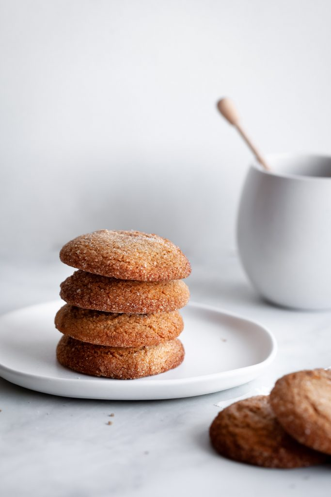 a head on image of a stack of 4 cookies with a white mug in the background.