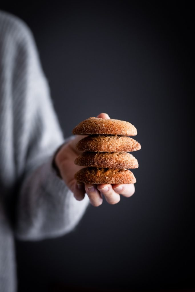 a hand holding a stack of 4 vegan spice cookies against a dark backdrop.
