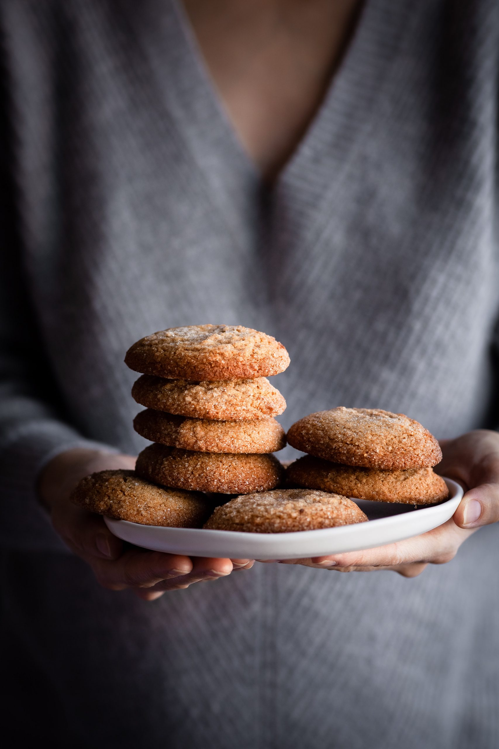 a person holding a plate of vegan ginger spice cookies.