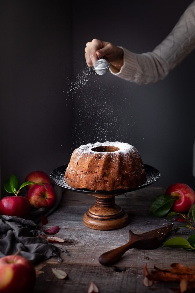 head on image of icing sugar being dusted onto cake.