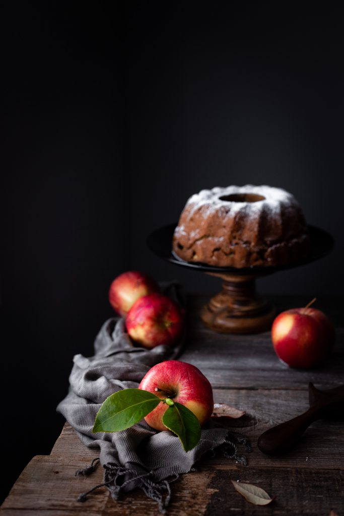 head on image of vegan apple spice cake on pedestal.