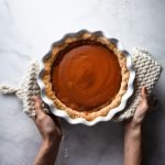 overhead image of vegan pumpkin pie with a baker holding it with two hands.