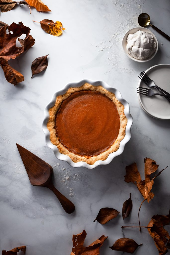 overhead image of vegan pumpkin pie with fall leaves and a pie lifter.