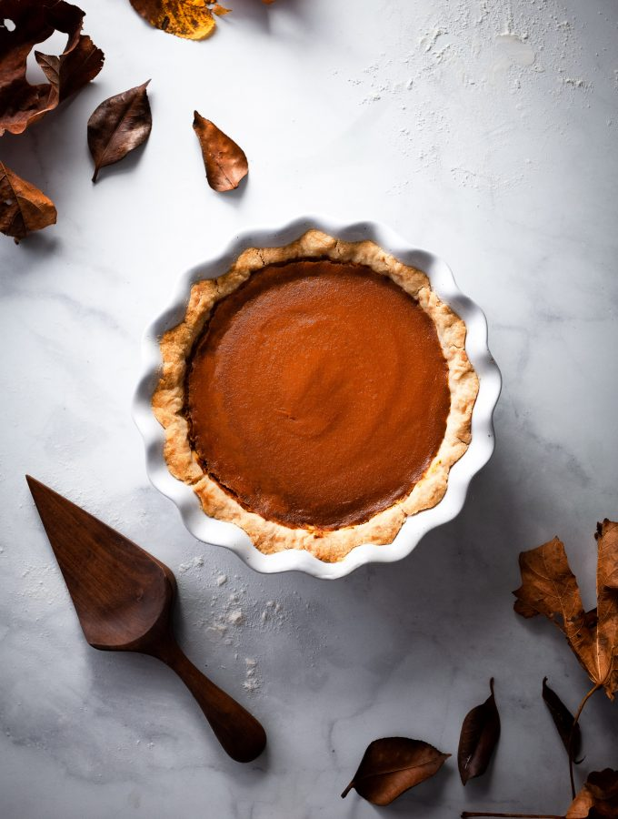 overhead image of pumpkin pie with fall leaves and a pie lifter.