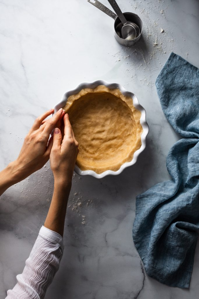 overhead image of baker pressing pie crust into a pie plate.