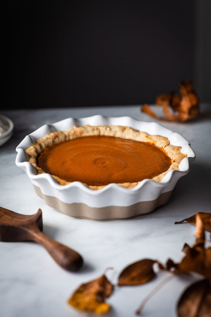 head on image of vegan pumpkin pie in a white pie plate and fall leaves in the foreground.