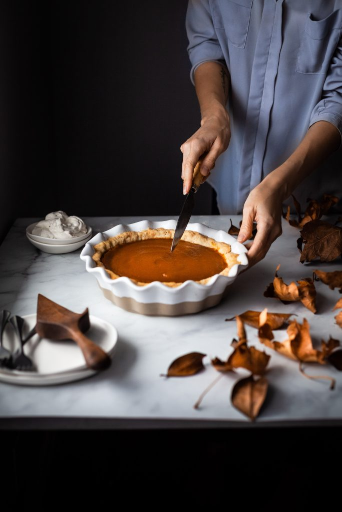 head on image of vegan pumpkin pie on a table with a baker about ti cut out a slice.