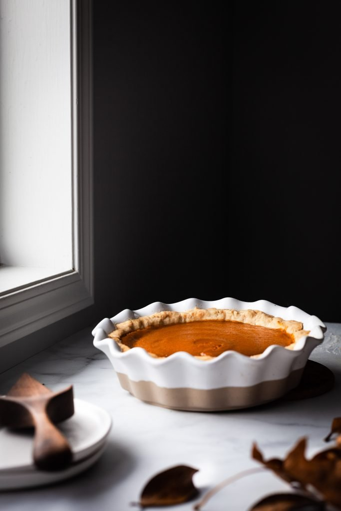 head on image of vegan pumpkin pie sitting by a window.