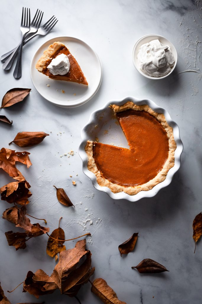 overhead image of vegan pumpkin pie with a slice on a plate.