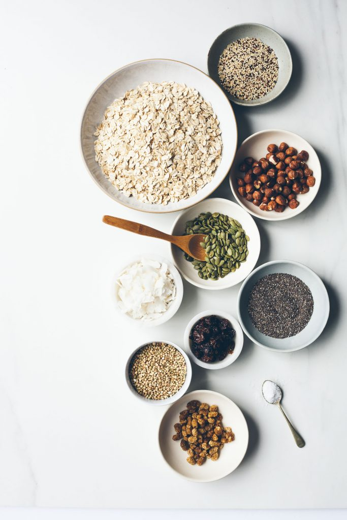 an overhead image of granola ingredients on a white surface.