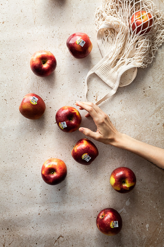 an overhead flatlay of a mesh bag with apples spilling out of it and a hand reaching for an apple.