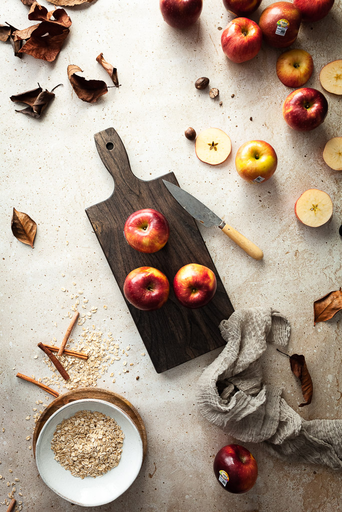 an overhead flatlay of apples on a walnut cutting board with apples, brown leaves, a bowl of oats and a brown linen towel around it.