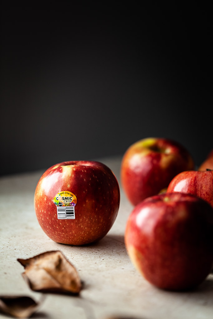 a closeup image of several apples on a table with brown leaves in the foreground.