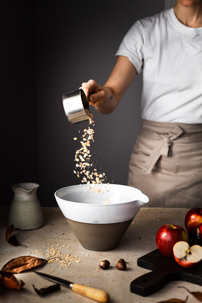 A person pouring rolled oats into a large white mixing bowl with apples on a cutting board on the right and a milk jug on the left.