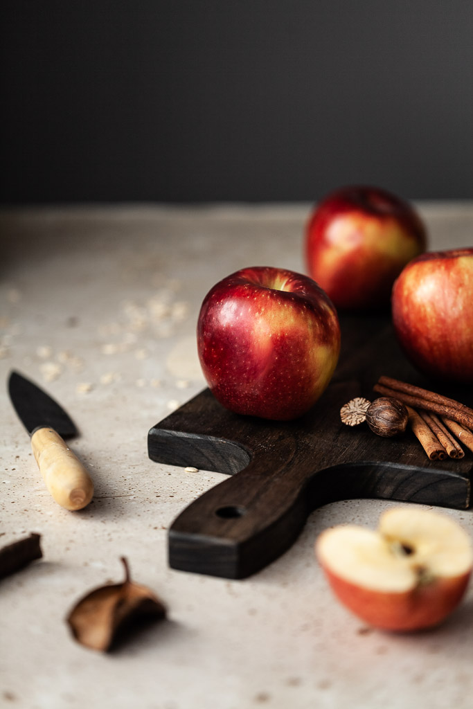 a close up of three apples on a cutting board with cinnamon sticks, nutmeg and a sliced apple on the right.