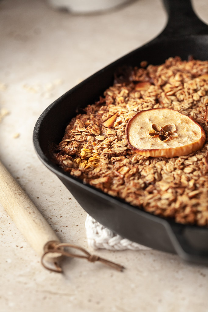 a close up angle of a cast iron pan filed with baked oatmeal and an apple ring ontop.