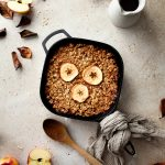 an overhead flatlay of baked oatmeal in a cast iron pan with a wooden spoon on the left and a milk jug and dishes in the upper right corner.