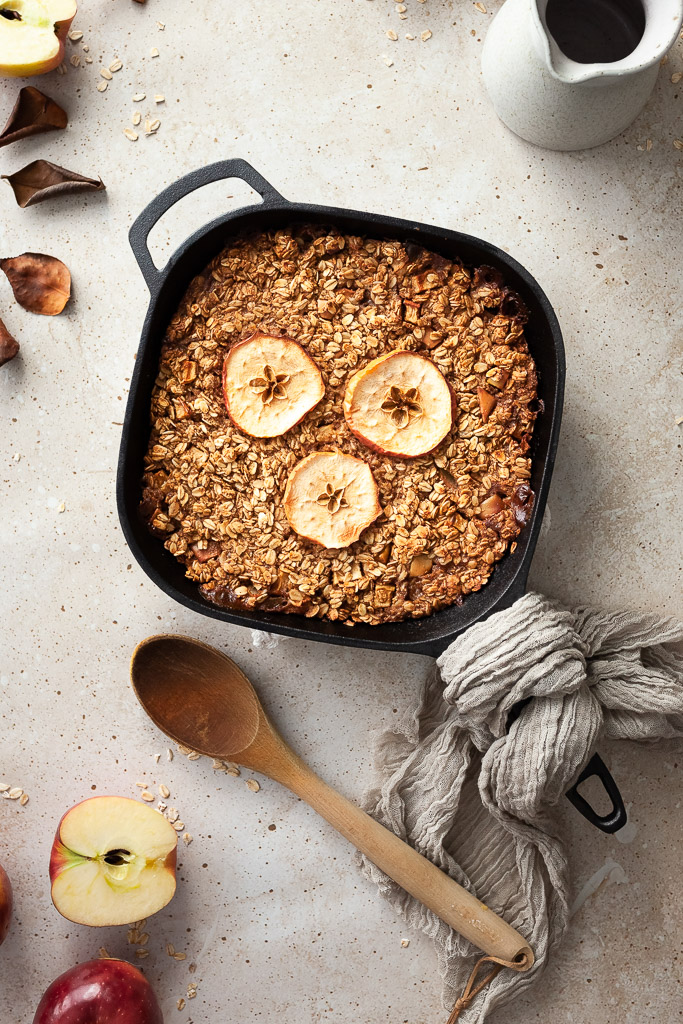an overhead flatlay of baked oatmeal in a cast iron pan with a wooden spoon on the left and a milk jug in the upper right corner.