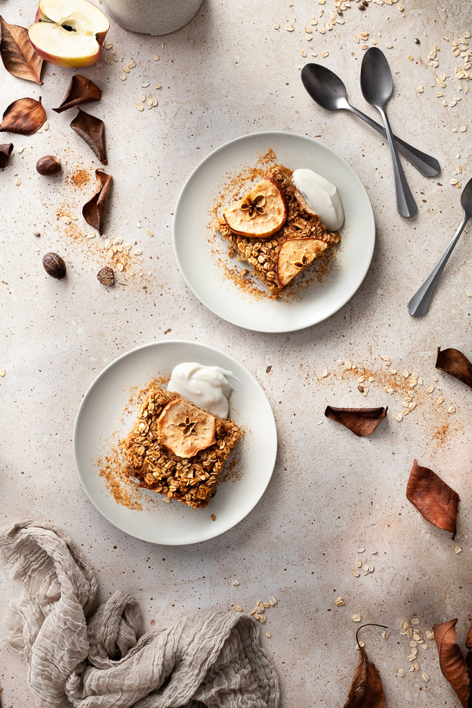 an overhead of two plates with spiced apple baked oatmeal and yogurt and spoons on the right.