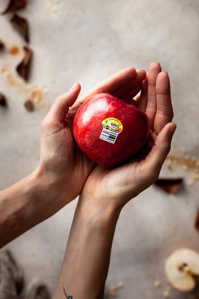 a closeup overhead image of hands cupping a red apple.