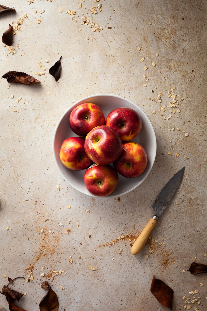 an overhead flatlay of 6 apples in a white bowl with a paring knife on the right and brown leaves.