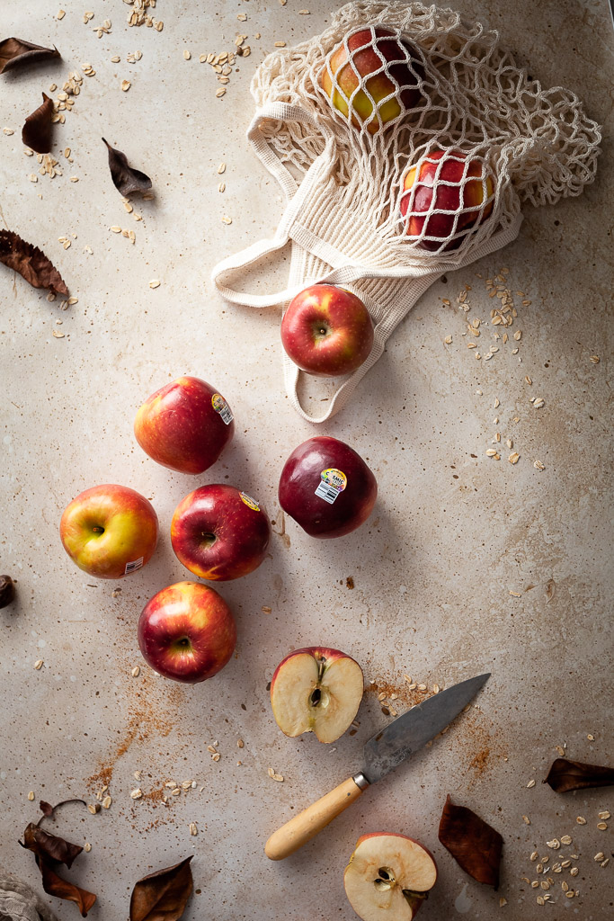 an overhead flatlay of apples and a mesh bag with a paring knife on the right and brown leaves.